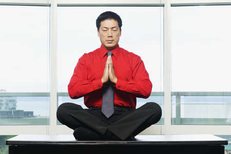 above 30: Businessman meditating in front of windows LANG_EVOIMAGES