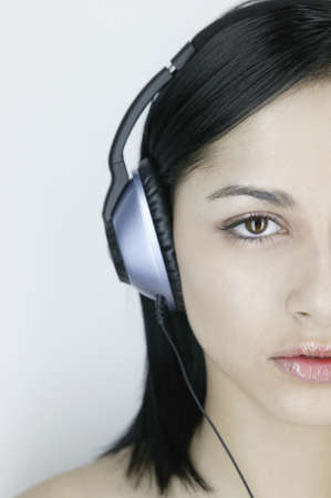above 18: Close-up of a young woman wearing headphones LANG_EVOIMAGES