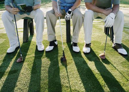 Golfspieler auf Bank sitzt LANG_EVOIMAGES