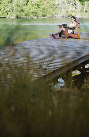 above 30: Teenage girl sitting on deck by lake reading LANG_EVOIMAGES