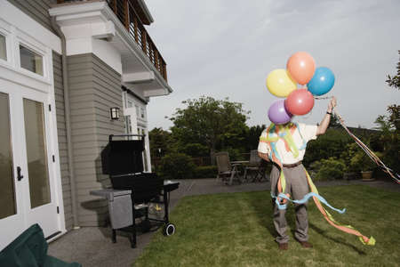 above 30: Portrait of man wearing birthday hat and streamers and holding balloons
