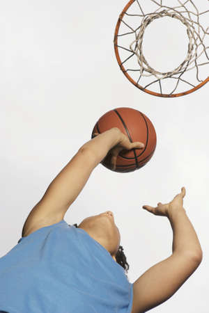 above 18: Low angle view of teenage girl shooting hoops LANG_EVOIMAGES