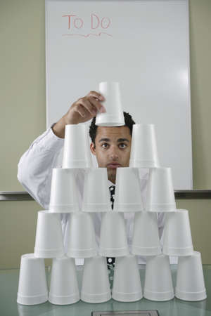 german ethnicity: Businessman building pyramid of styrofoam cups LANG_EVOIMAGES