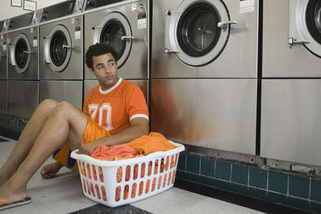 laundromat: Man sitting on floor with clothes in laundromat LANG_EVOIMAGES