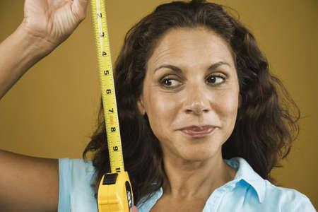 hermosa beach: Woman looking sideways holding tape measure