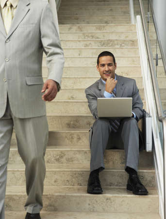 telecommunicate: Businessman sitting on steps with laptop