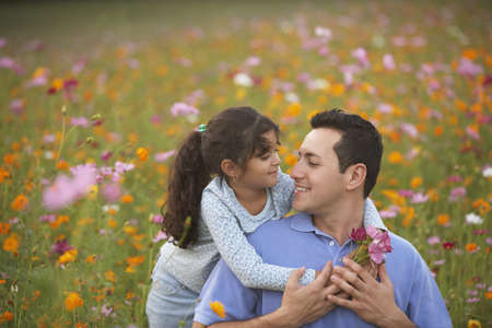 some under 18: Girl hugging her father in field of flowers