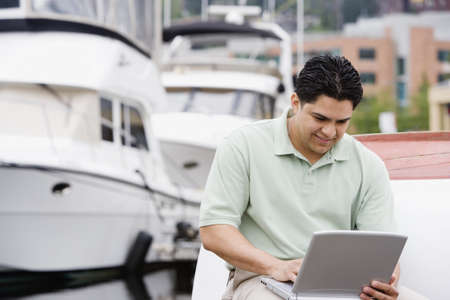 sawhorse: Man sitting by dock with laptop