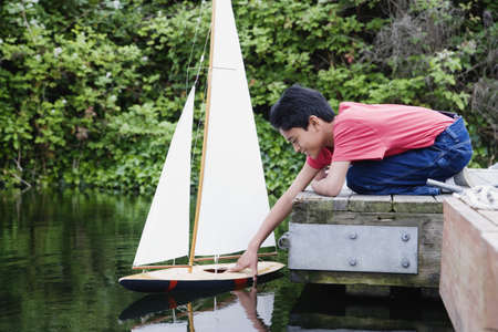 above 30: Side view of boy on docks with toy sailboat in water