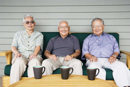 above 30: Portrait of three elderly men sitting on couch drinking coffee