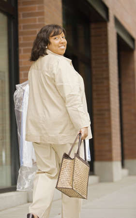 dry cleaning: Rear view portrait of woman walking down street with dry cleaning LANG_EVOIMAGES