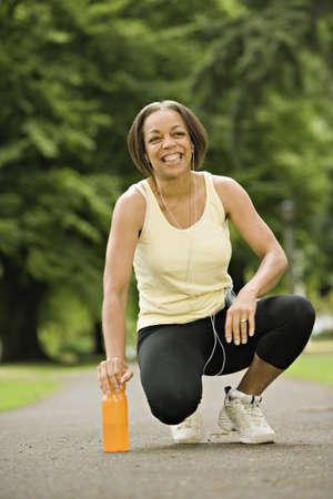 mujer arrodillada: Mujer que se arrodilla en la botella de agua en el parque