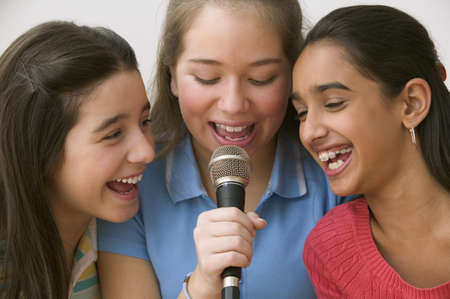 three girls: Three girls singing with microphone
