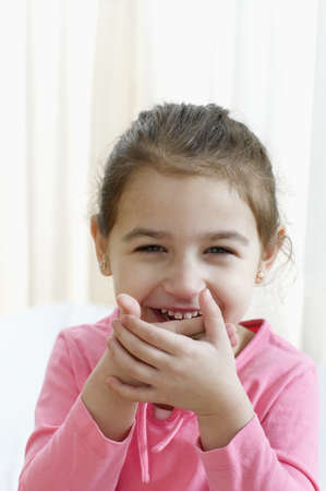 all under 18: Portrait of young girl laughing with hands over her mouth LANG_EVOIMAGES