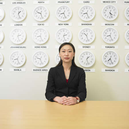 time zone: Businesswoman with time zone clocks on the wall behind her LANG_EVOIMAGES