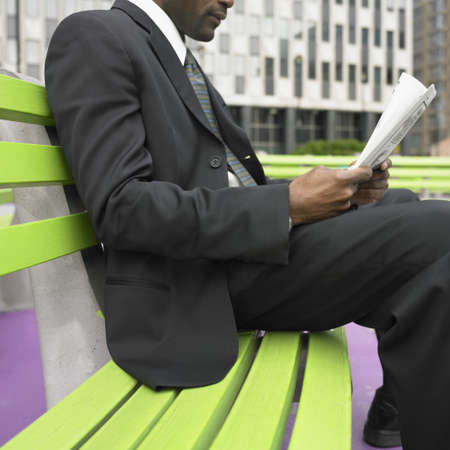 above 30: Midsection of businessman sitting on bench reading newspaper LANG_EVOIMAGES