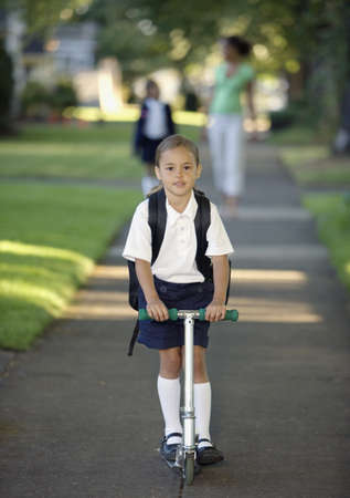 some under 18: Portrait of girl in school uniform on scooter LANG_EVOIMAGES