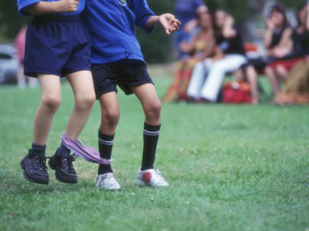 legs: Low section of two boys in three-legged race