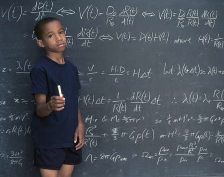 rebelling: Portrait of boy holding chalk while standing in front of chalkboard