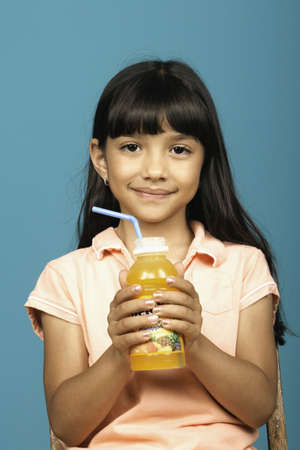 some under 18: Young girl holding bottle of juice
