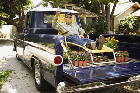 leaning on the truck: Portrait of elderly man in lounge chair and sunglasses relaxing in back of pickup truck