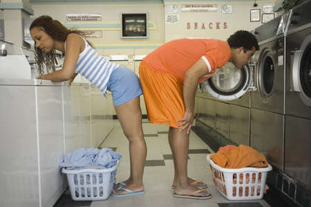 above 25: Couple bent over washer and dryer in laundromat