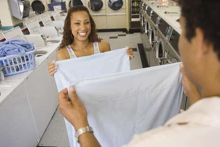 laundromat: Couple folding sheets in laundromat