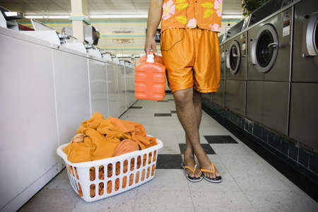 laundromat: Low section of man with soap and laundry in laundromat