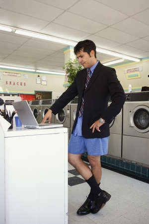laundromat: Businessman in shorts with laptop at laundromat