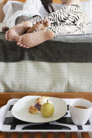 lovemaking: Couples feet laying in bed with breakfast LANG_EVOIMAGES