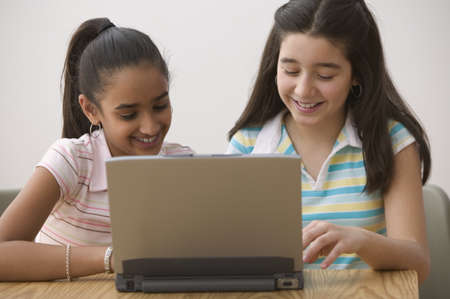 all under 18: Two girls sitting with laptop computer