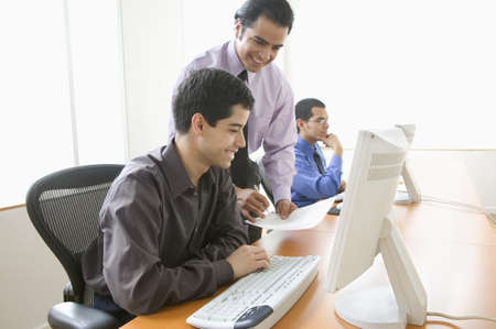 above 18: Three businessmen in office with computer