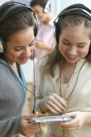 all under 18: Two teenage girls with headsets listening to music LANG_EVOIMAGES