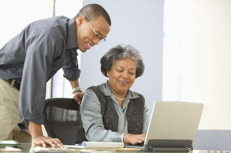 above 25: Man leaning over desk of mature woman with computer LANG_EVOIMAGES