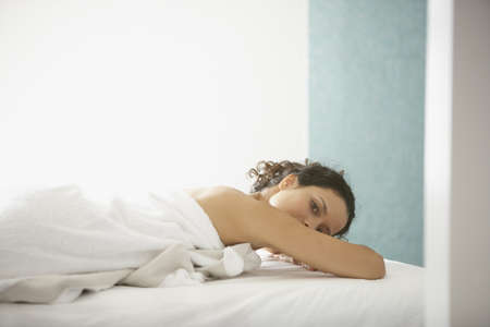 only mid adult women: Portrait of woman wrapped in towel laying on bed LANG_EVOIMAGES