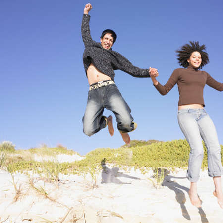 above 30: Young couple jumping off a sand dune