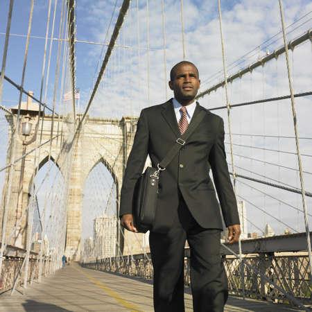 above 30: Low angle of businessman walking across bridge