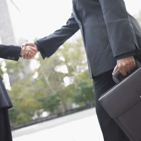 three people only: Low angle view of businesswomen shaking hands LANG_EVOIMAGES