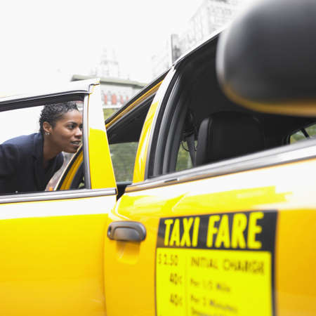 above 30: Businesswoman getting into cab