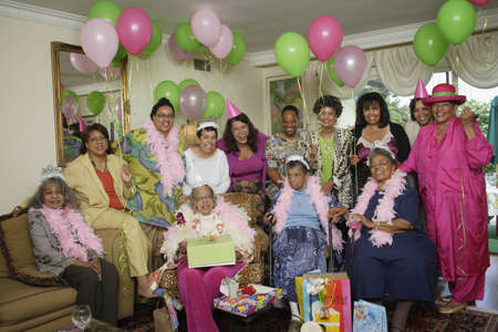 Group portrait of senior adult birthday party with balloons LANG_EVOIMAGES