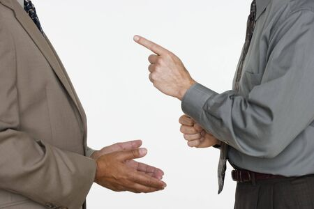 lecturing: Mid section of two businessmen facing each other with hands gesturing