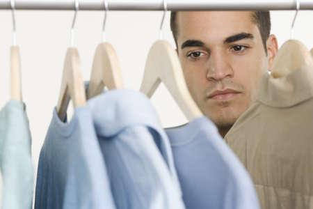 Man looking at shirts in  closet Stock Photo
