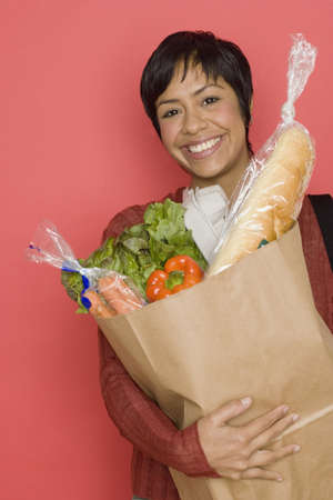 woman holding bag: Portrait of woman holding bag of groceries