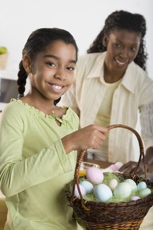 some under 18: Portrait of girl holding Easter eggs in basket with mother looking at her