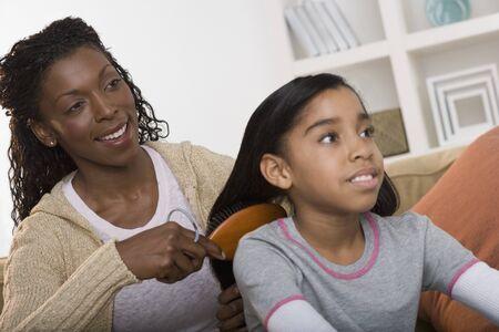 some under 18: Mother brushing daughter hair
