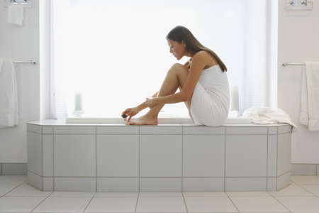 woman in bath: Woman wrapped in towel painting toenails on side of tub