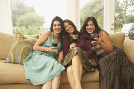 woman on couch: Portrait of three women sitting on couch with wine glasses