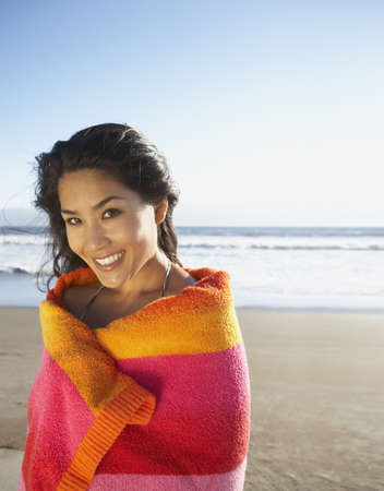 above 25: Portrait of woman wrapped in towel at beach