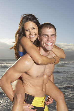 wetting: Man giving woman piggy back ride at beach LANG_EVOIMAGES
