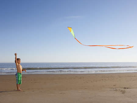 all under 18: Boy flying kite at beach